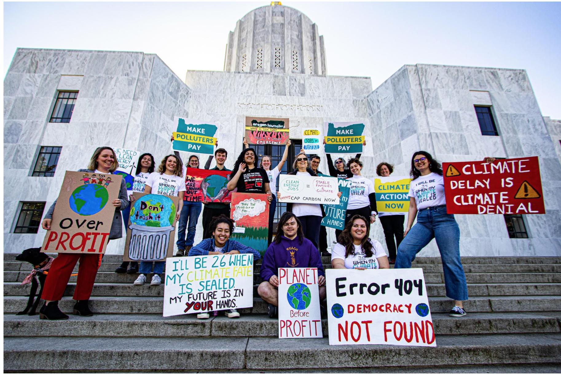A group of people standing in front of the Oregon State Capitol holding signs stating that climate change is an emergency.